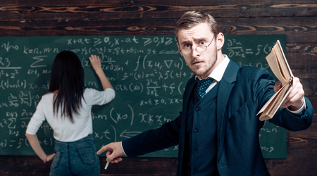 Genius man in glasses with book point at woman solving equation on chalkboard. Genius teacher with student in classroom. Stock Photo