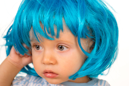 Pure beauty. Adorable little child in fashion wig. Small child wear blue wig hair. Small kid in fancy wig hairstyle. Cute baby with long blue hair. Beauty look hairstyle for cosplay party. Banco de Imagens