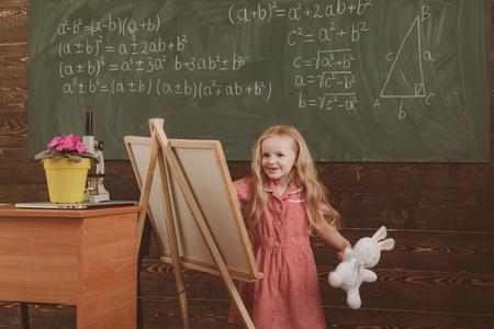 Girl draw picture in art school. Little artist paint on studio easel, art education, vintage filter. Archivio Fotografico - 115468638