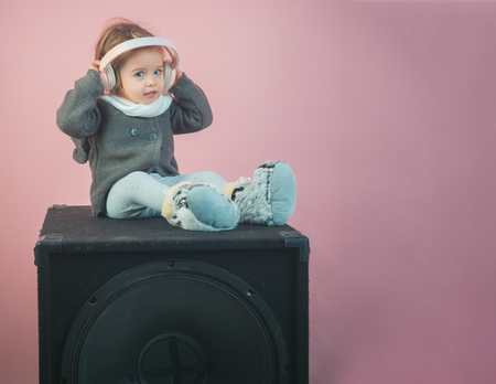 small happy girl. audio speaker. winter kid fashion. having fun. little girl child smiling. childhood and happiness. kid listen music with headset and mp3 on phone. Young expertise. Feeling free.
