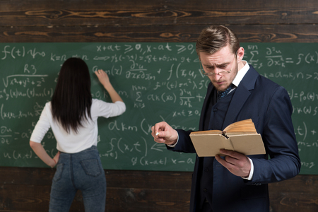 School day. Teacher man in glasses read problem statement from textbook to girl student. Learning math enables me to think clearly. Rear view woman write equation on chalkboard. Doing sums.