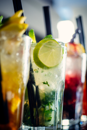 Drinking hours. Juicy beverages with alcohol on counter. Cocktails served in glasses with drinking straws. Iced drinks in cocktail glasses in bar. Alcoholic mixed drinks with ice. Alcohol addiction. Stock Photo