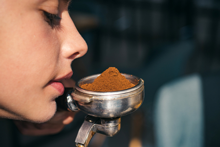 Enjoying coffee fragrance and aroma. Woman sniff the smell of fresh ground coffee. Woman barista hold portafilter in hand. Barista brew espresso coffee drink. Brewing coffee device.