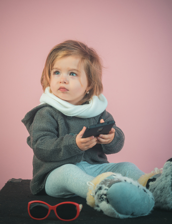 having fun. kid listen music with headset and mp3 on phone. winter kid fashion. small happy girl. little girl child smiling. childhood and happiness. Looking trendy. Hip hop girl. Stock Photo