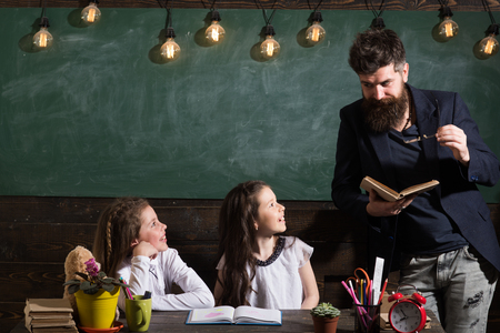 Curious cheerful children listening teacher with attention. Teacher and girls pupils in classroom, chalkboard on background. Man with beard teaches schoolgirls, reading book. Primary school concept