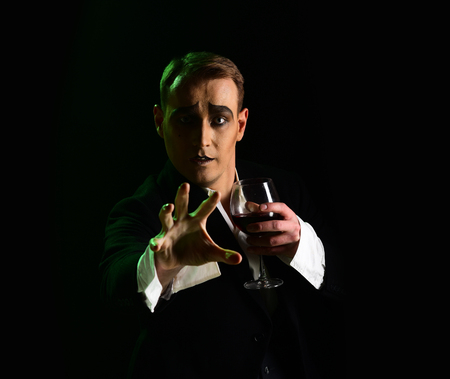 Wait. Mime artist perform on stage. Stage actor pantomime drinking wine. Comedian with mime makeup hold wine glass. Drama theatre actor miming. Theatrical performance art and silen comedy. Mime man.
