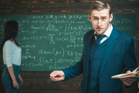 It is unbelievable. Man with book and glasses on surprised face while woman stand at chalkboard. Education in university or home schooling. Unexpected solution. Can you imagine that. School day. Stock Photo