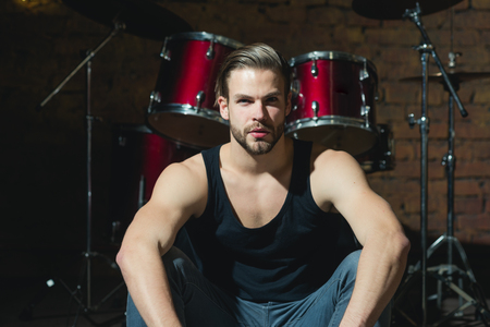 Beat of drums. Rock star or rocker. Enjoying instrumental music. Handsome man sit on stage at percussion instrument. Man drummer at musical instrument. Rock concert or rehearsal in music club. Stockfoto