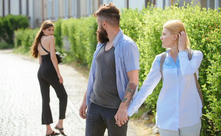 He is a cheater. Man cheating his wife or girlfriend. Love triangle and threesome. Bearded man looking at other girl. Hipster choosing between two women. Betrayal and infidelity. Unfaithful love.