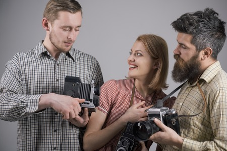 He got some great shots. Retro style woman and men hold analog photo cameras. Group of photographers with retro cameras. Paparazzi or photojournalists with vintage old cameras. Photography studio. Stock Photo