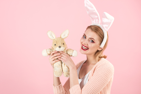Spring holiday. Girl with hare toy. Happy easter. Woman in rabbit bunny ears. Egg hunt. Easter eggs as traditional food. happy woman in bunny ears with toy. Look over there. Stock Photo