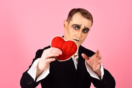 He is sensitive and very poetic. Mime man hold red heart for valentines day. Theatre actor pantomime falling in love. Mime actor with love symbol. Love confession on valentines day.