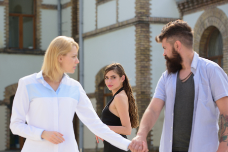 Being odd woman out. Love triangle and threesome. Bearded man looking at other girl. Hipster choosing between two women. Man cheating his wife or girlfriend. Betrayal and infidelity. Unfaithful love.