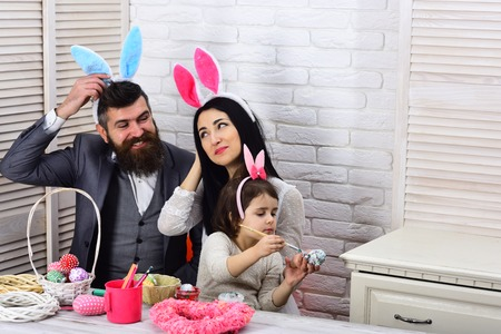Happy easter. Childhood. Egg hunt on spring holiday. Family love easter. Mother, father and daughter paint easter eggs. Rabbit family with bunny ears. Easter day. Stockfoto