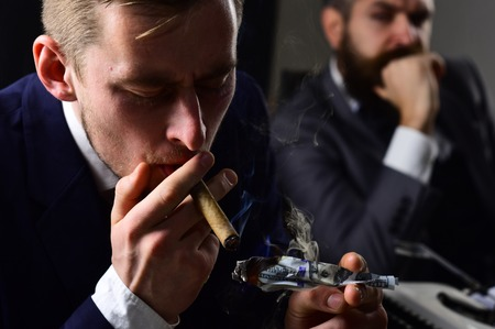 He has megabucks. Businessmen have money to burn. Man light up cigar from money banknote. Rich man smoking during business meeting. Business partners writing financial report. Waste of money. Zdjęcie Seryjne