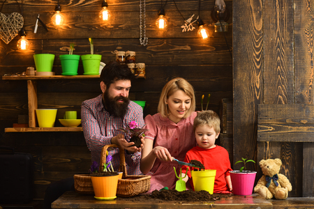 woman, man and little boy child love nature. Flower care watering. Soil fertilizers. Family day. Greenhouse. happy gardeners with spring flowers. Father and son with mother. Having fun. Foto de archivo - 118379301