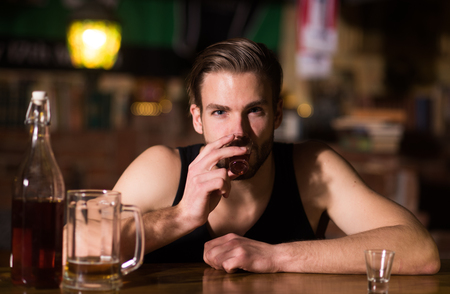 A regular alcohol drinking. Alcohol addict with short alcohol drink. Alcoholic man drinking at bar counter. Man drink strong alcoholic beverage and beer in pub.