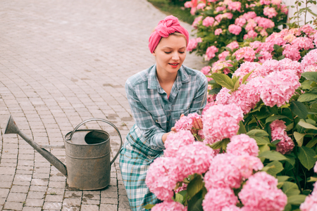 hydrangea. Spring and summer. happy woman gardener with flowers. Flower care and watering. soils and fertilizers. woman care of flowers in garden. Greenhouse flowers. I love my job.