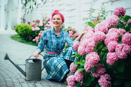 woman care of flowers in garden. Flower care and watering. soils and fertilizers. Greenhouse flowers. happy woman gardener with flowers. hydrangea. Spring and summer. Making the world green. Foto de archivo - 118380447
