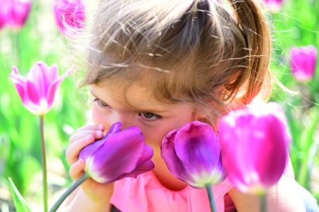 Spring in pot. Small child. Natural beauty. Childrens day. Summer girl fashion. Happy childhood. Springtime tulips. weather forecast. face and skincare. allergy to flower. Little girl in sunny spring. Stock Photo