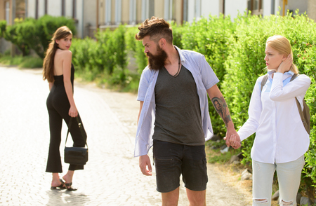 He loves ladies. Bearded man looking at other girl. Love triangle and threesome. Man cheating his wife or girlfriend. Hipster choosing between two women. Betrayal and infidelity. Unfaithful love.