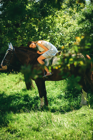 Taming and training. Pretty woman riding horse on summer landscape. Cute girl at horse ranch. Adorable horse owner with her pet. Making friends with horse. Being a good horsewoman.