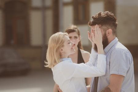 Bärtiger Mann betrügt seine Frau mit einem anderen Mädchen. Unglückliches eifersüchtiges Mädchen. Standard-Bild