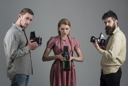 Save best moments. Retro style woman and men hold analog photo cameras. Photography studio. Group of photographers with retro cameras. Paparazzi or photojournalists with vintage old cameras.