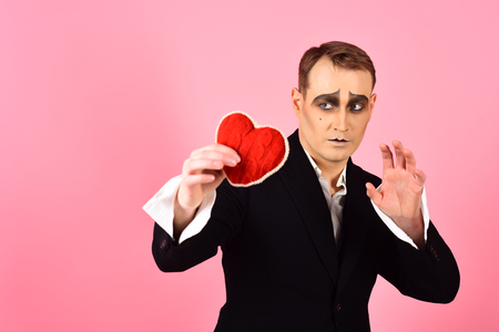 His story of boundless love. Theatre actor pantomime falling in love. Mime actor with love symbol. Mime man hold red heart for valentines day. Love confession on valentines day.