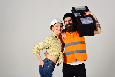 Accuracy of fixing. Pretty woman and bearded man in workwear. Builders or building technicians hold repair kit. Couple of construction workers. Renovation and construction. Couple of hard workers. Stock Photo