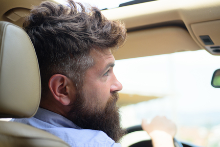 Green tech. Bearded man travel by automobile transport. Hipster enjoying road trip. Eco driving is an ecologic driving style. Eco friendly and sustainable travel. Travelling by road transport. Stock Photo