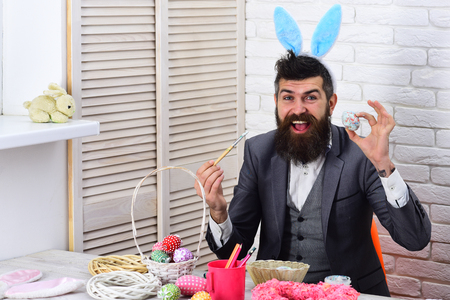 Rabbit man with bunny ears. brutal male with beard. Bearded man hipster paint easter eggs. Egg hunt on spring holiday. love easter. Happy easter. Funny bunny. Easter dinner. Stock Photo