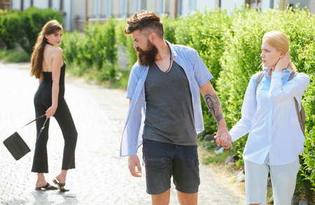 Estás conmigo. Hipster eligiendo entre dos mujeres. Triángulo amoroso y trío. Hombre engañando a su esposa o novia. Hombre barbudo mirando a otra chica. Traición e infidelidad. Amor infiel.