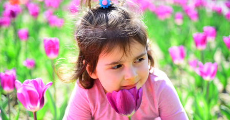 face and skincare. allergy to flowers. Small child. Natural beauty. Childrens day. Little girl in sunny spring. Summer girl fashion. Happy childhood. Springtime tulips. weather forecast. Green plant.