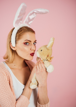Woman in rabbit bunny ears. Egg hunt. Easter eggs as traditional food. Spring holiday. Girl with hare toy. happy woman in bunny ears with toy. Happy easter. Ester bunny hunt begins