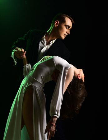 More than a little romance. Theatre actors miming through body motions. Couple of mime artists perform romance on stage. Couple in love with mime makeup. Mime man and woman act in romantic scene. Stock Photo