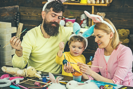 Happy easter! Mother, father and her child enjoy painting Easter eggs. Stock Photo - 117728685