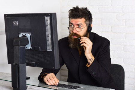 Can I help you. Responding the calls from customers. Call center operator at work. Bearded man working in office. Man with long beard and headphones. Bearded company representative at computer.
