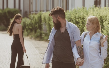 Ladies man. Bearded man looking at other girl. Hipster choosing between two women. Love triangle and threesome. Man cheating his wife or girlfriend. Betrayal and infidelity. Unfaithful love. Stock Photo - 122566982