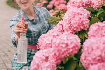 happy woman gardener with flowers. Greenhouse flowers. Flower care and watering. soils and fertilizers. hydrangea. Spring and summer. woman care of flowers in garden. Flowers need good care. Foto de archivo - 118684889