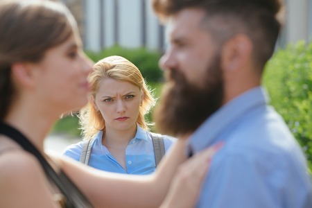 She has reason to be jealous. Unhappy girl feeling jealous. Romantic couple of man and woman dating. Bearded man cheating his woman with another girl. Jealous woman look at couple in love on street.