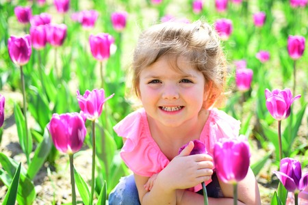 Express positivity. Small child. Natural beauty. Childrens day. Summer girl. Happy childhood. Springtime tulips. weather forecast. face and skincare. allergy to flowers. Little girl in sunny spring.