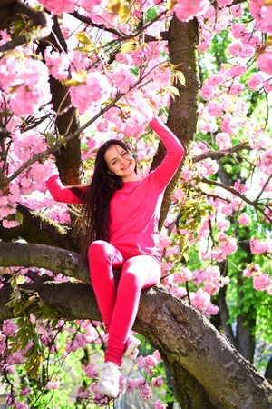 Her individual fashion sense. Fashionable young lady on flowering tree. Fashion clothing for spring. Little girl in fashion wear in spring garden. Pretty girl with fashion look. 写真素材