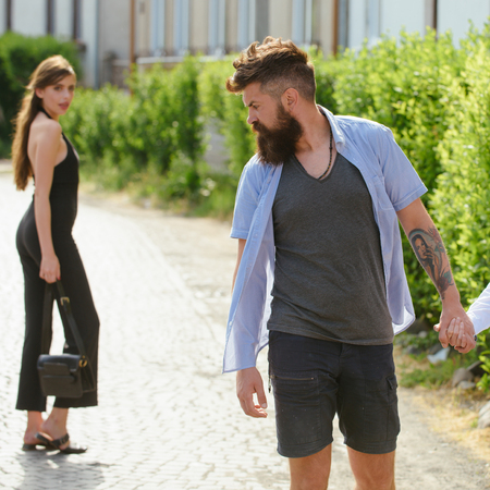Feeling flirtatious. Bearded man and cute woman walk on street. Hipster look back at pretty woman. Couple in love on summer day. Enjoying the flirtation. Romantic date and dating. Little flirtation.