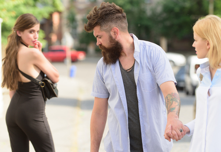 Flirting in the street. Love triangle and threesome. Man cheating his girlfriend. Bearded man looking at other girl. Hipster choosing between two women. Betrayal and infidelity. Unfaithful love. Stock Photo - 117756128