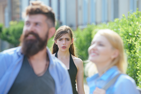 She is jealous. Unhappy girl feeling jealous. Bearded man cheating his girlfriend with another woman. Jealous woman look at couple in love on street. Romantic couple of man and woman dating. Stock Photo - 117756130