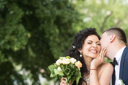 Newlywed man kiss happy woman with bouquet. Newlywed couple smile on summer outdoor.