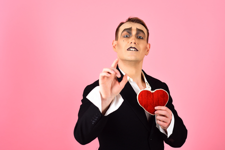 Telling love story. Mime actor with love symbol. Mime man hold red heart for valentines day. Theatre actor pantomime falling in love. Love confession on valentines day.
