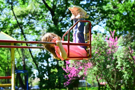 romantic little girl on the swing, sweet dreams. Small kid playing in summer. childhood daydream .teen freedom. Playground in park. Happy laughing child girl on swing. Happy spring day. Banco de Imagens