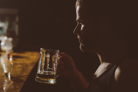 A cold beer after work. Handsome man drink beer at bar counter. Man drinker in pub. Alcohol addict with beer mug. Beer restaurant. Alcohol addiction and bad habit. Addicting to alcoholic drink. Stock Photo